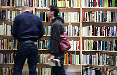 Menschen vor gefüllten Buchregalen auf einer Messe - Foto: Martina Berg