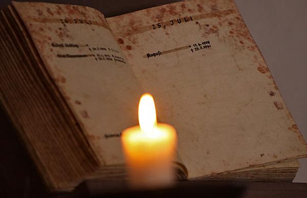 Kerze vor einem Totenbuch